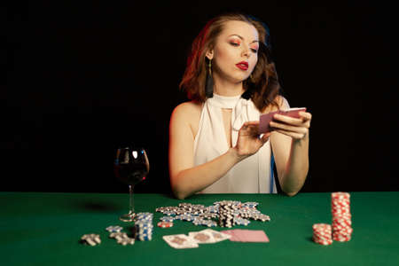 Emotional young girl in a white blouse drinking wine from a glass and playing cards on a table on green cloth in a casino