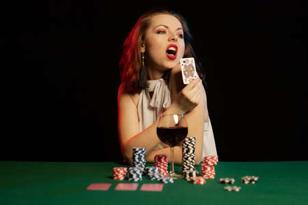Emotional young lady in a white blouse drinking wine from a glass and playing cards on a table on green cloth in a casino