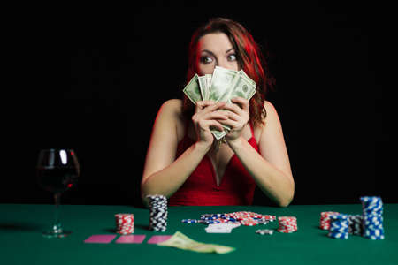 Emotional woman in an evening red dress playing cards with money on the table on a green cloth in a casino