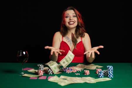 Emotional young lady in an evening red dress playing cards on a table on green cloth in a casino Archivio Fotografico