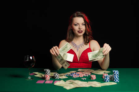 Emotional young lady in an evening red dress playing cards on a table on green cloth in a casino Foto de archivo