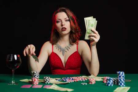 Emotional young lady in an evening red dress playing cards on a table on green cloth in a casino 写真素材 - 152066648