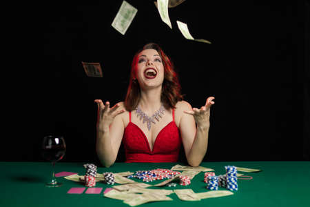 Emotional young lady in an evening red dress playing cards on a table on green cloth in a casino 写真素材 - 152066657