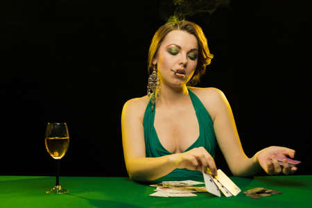 A young lady in a green dress plays cards on a table on green cloth