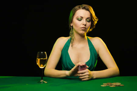 A young lady in a green dress smokes a cigarette and blows smoke and plays cards on a table on green cloth