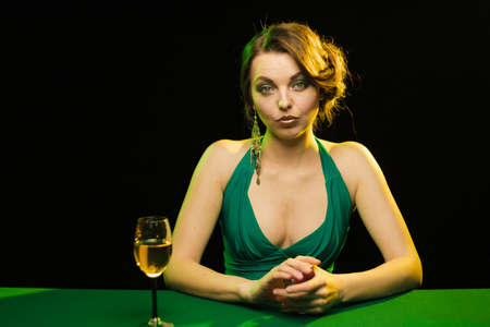 A young lady in a green dress playing cards on a table on a green cloth in a casino