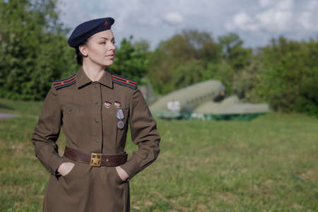 A young female pilot in uniform of Soviet Army pilots during the World War II. Military shirt with shoulder straps of a major and a beret. Against the background of a military aircraft. 写真素材 - 152192019
