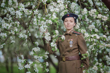 A young female pilot in uniform of Soviet Army pilots during the World War II. Military shirt and a beret. In spring blooming apple orchard
