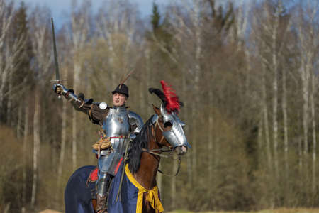 adult man in ancient knight armor rides across the field on a horse in armor in red and blue blanket