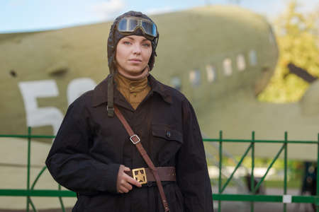 A young female pilot in uniform of Soviet Army pilots during the World War II. Black flying jumpsuit, helmet and goggles. Photo in retro style.