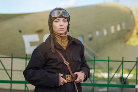 A young female pilot in uniform of Soviet Army pilots during the World War II. Black flying jumpsuit, helmet and goggles. Photo in retro style. Standard-Bild