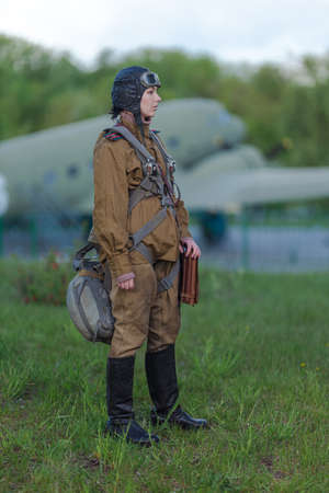 A young female pilot in uniform of Soviet Army pilots during the World War II. Military shirt with shoulder straps of a major, parachute, flight helmet and goggles.