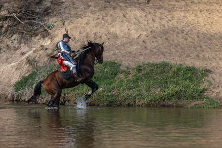 A young adult man in knightly armor rides a horse on a river along a sandy shore