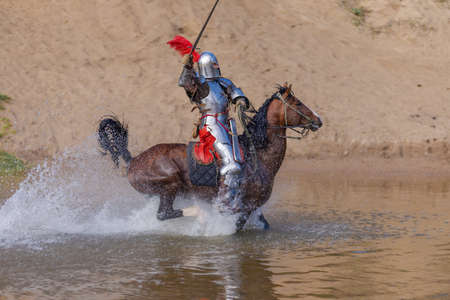 A young adult man in knightly armor rides a horse on a river along a sandy shore Stock Photo