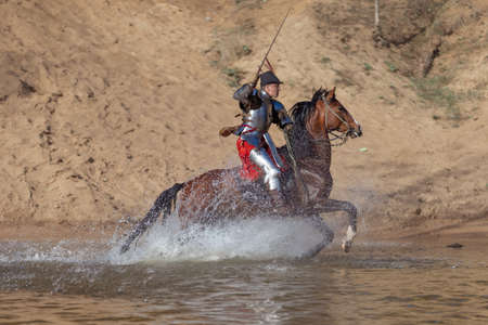 Adult man in ancient knight armor with a sword rides a horse on a river along a sand shore and poses Stock Photo