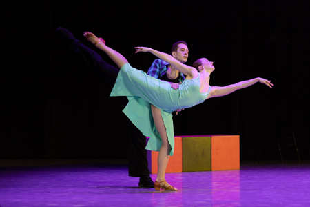 A pair of dancers a man and a woman perform in a theater on stage in a dance musical show.