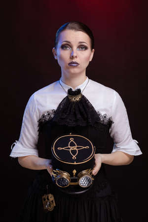 Emotional woman in steampunk costume posing in blue and red stage light