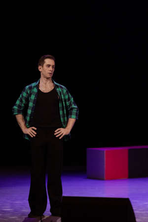 Actor dancer young man performs in the theater on stage in a dance musical show