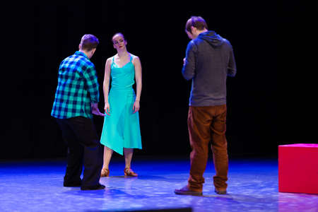 A pair of dancers a man and a woman are dancing on stage and a man videographer records a video clip and reports.