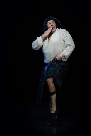 Emotional Man with a beard in a blue checkered Scottish costume posing on a black background