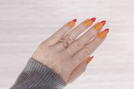 Female hand with long nails and yellow, orange and red gradient manicure