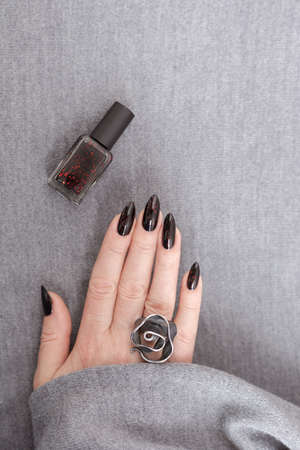 Female hand with long nails and gray black manicure with bottles of nail polish