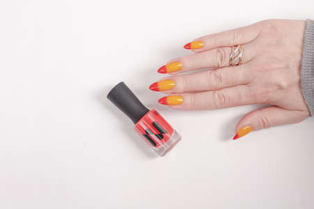 Female hand with long nails and yellow, orange and red gradient manicure and a bottle of nail polish