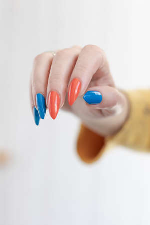 Female hand with long nails and multi-colored bright bottle manicure with nail polish and pen markers