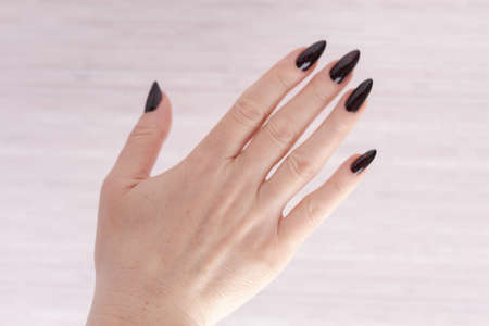 Female hand with long nails and gray black manicure
