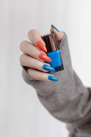 Female hand with long nails and colored bright bottle manicure