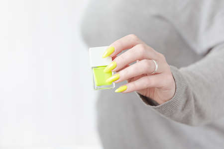 Female hand with long nails and a bottle of bright neon yellow green nail polish 免版税图像
