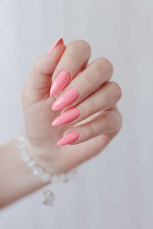 Woman's hands with long nails and pink fuchsia bottle manicure with nail polish Imagens