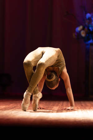 Young girl gymnast performs with a performance on stage in a theater