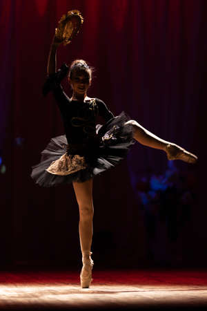 Young girl ballerina in a black tutu dress dancing performance on stage in a theater on a red background