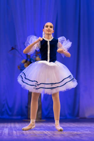 Young girls ballerina in a blue and white costume dancing performance on stage in a theater