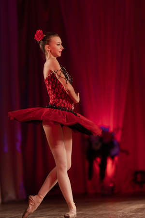 Young girl ballerina in a red tutu performs with a performance on stage in a theater Banque d'images