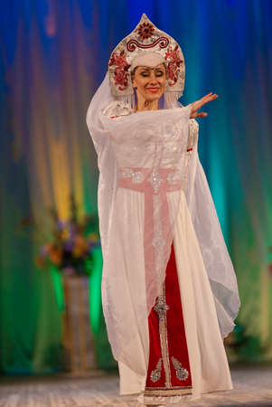 Young woman ballerina in a white suit with a crown on her head performs with a performance on stage in a theater