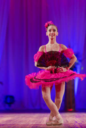 Young girl ballerina in a pink tutu performs with a performance on stage in a theater