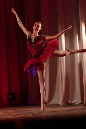 Young girl ballerina in a red tutu performs with a performance on stage in a theater
