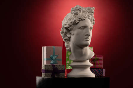 Statue of Apollo Belvedere, gifts boxes and packages, spotlights and multi-colored backgrounds.