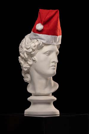 White Plaster Statue of Apollo Belvedere in a red cap of Santa Claus