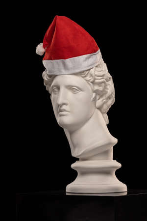 White Plaster Statue of Apollo Belvedere in a red cap of Santa Claus