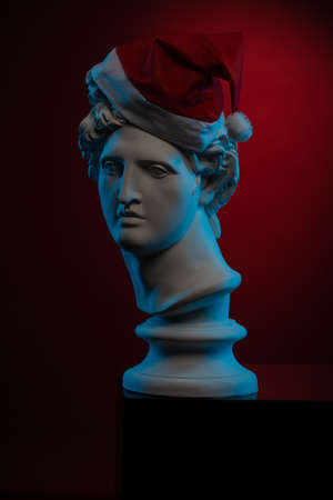 White gypsum Statue of Apollo Belvedere in a red cap of Santa Claus in blue contour light on colorful backgrounds.
