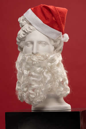 White plaster Statue of Apollo Belvedere with a long white beard and in a red cap of Santa Claus Reklamní fotografie