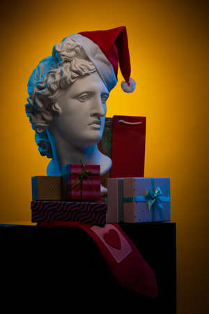 White plaster Statue of Apollo Belvedere in a red cap of Santa Claus, gifts boxes and packages on colorful backgrounds. Composition for congratulations, background for design.
