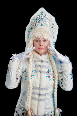 Snow Maiden in a white fur coat and kokoshnik poses on a black background