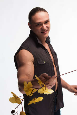 Portrait of a brutal man bodybuilder athlete with a sprig of blooming yellow orchid in hands on a white background