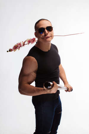 Portrait of a brutal man bodybuilder athlete in sunglasses with a sprig of blooming pink orchid in hands on a white background 写真素材
