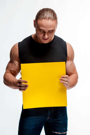 Portrait of a brutal man bodybuilder athlete with a sheet of paper for notes in the hands on a white background 写真素材
