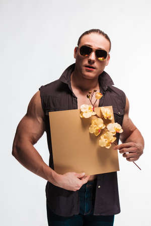Portrait of a brutal man bodybuilder athlete with a sprig of blooming yellow orchid and paper for notes in the hands on a white background